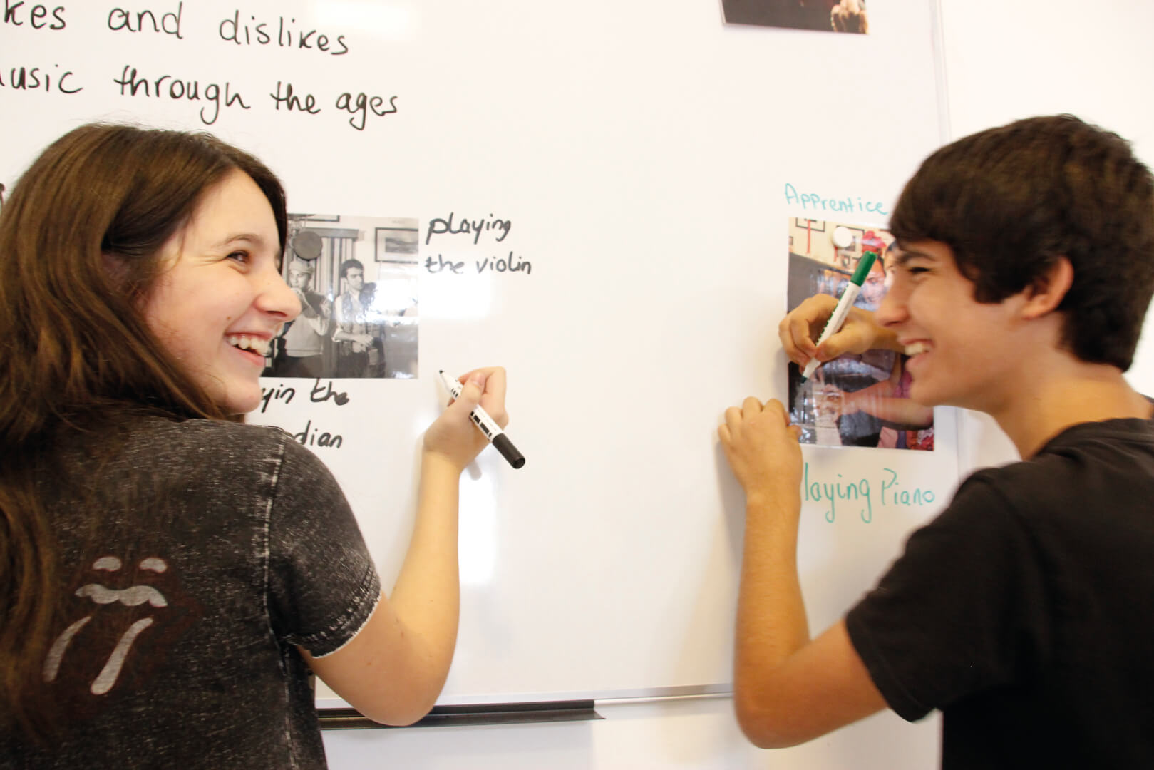 2 young English language students laughing and writing on a board.