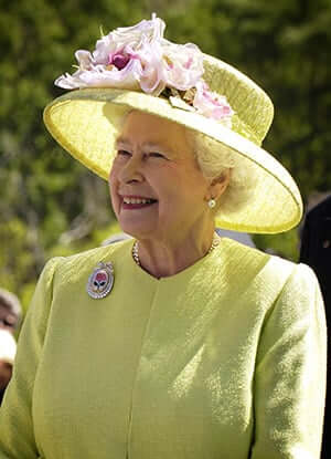 The Queen of England smiling and wearing a yellow outfit with matching hat.