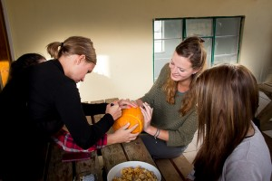 Happy studetns carving Halloween pumpkins