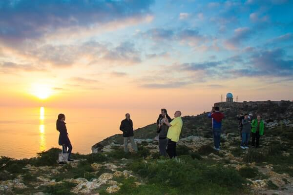 Students watching a winter sunset at Dingli Cliffs.